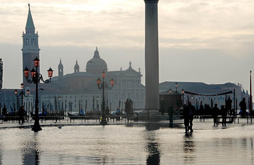 22. Люди идут по площади Сан Марко на второй день наводнения в Венеции 2 декабря 2008 года. (ANDREA PATTARO/AFP PHOTO)