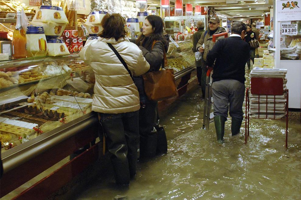 25. Покупатели стоят в полузатопленной кондитерской в Венеции 1 декабря 2008 года. Туристам и жителям города пришлось ходить по затопленным улицам на деревянных настилах. Метеослужба «Centro Maree» сообщила, что уровень Адриатического моря поднялся на 1,56 метров. (REUTERS/Michele Crosera)