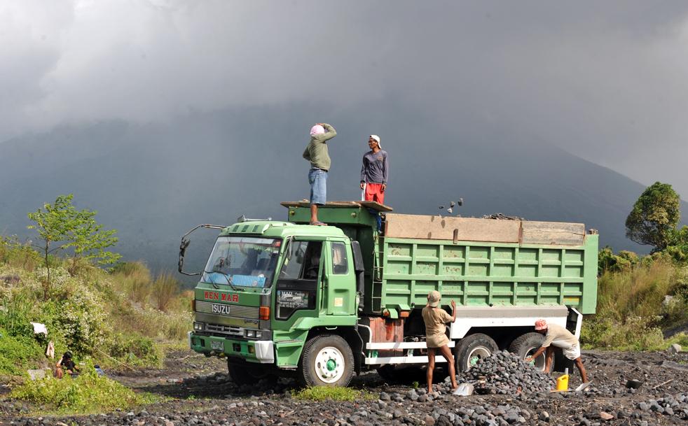 3. Рабочие грузят вулканические камни недалеко от подножия вулкана Майон (на заднем плане) в городе Гинобатан, провинция Албай, 21 декабря. (AFP/Getty Images/Ted Aljibe)