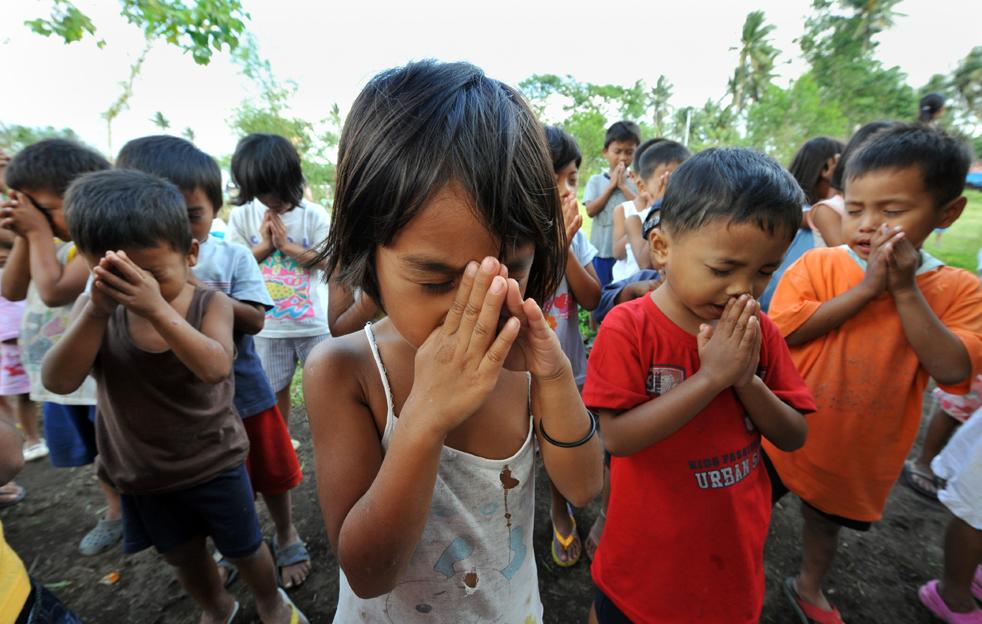 4. Эвакуированные с подножия извергающегося вулкана Майон дети молятся во временном убежище в деревне недалеко от города Гуинобатан в провинции Албай 21 декабря. (AFP/Getty Images/Ted Aljibe)