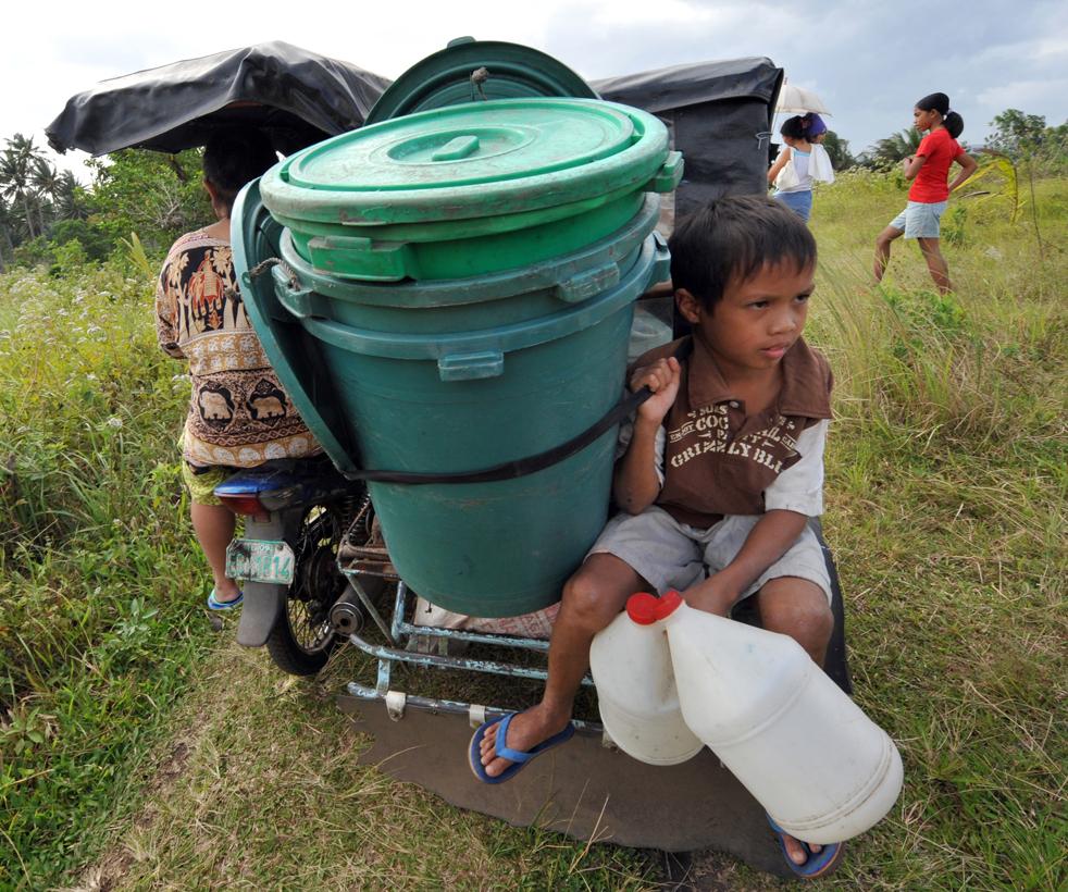 5. Мальчик едет на велосипеде с вещами своей семьи, пока жители покидают населенный пункт у подножия вулкана Майон в провинции Албай 21 декабря. (AFP/Getty Images/Ted Aljibe)