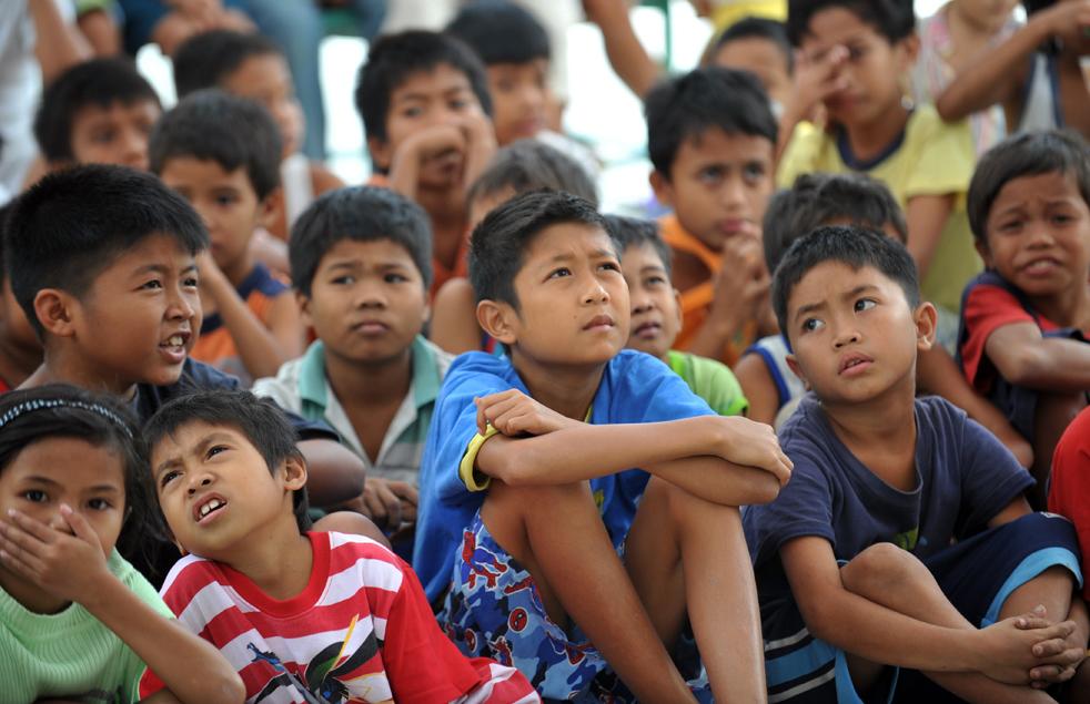 6. Эвакуированные с территорий извергающегося вулкана Майон дети смотрят телевизор во временном убежище в городе Гуинобатан в провинции Албай 21 декабря. (AFP/Getty Images/Ted Aljibe)