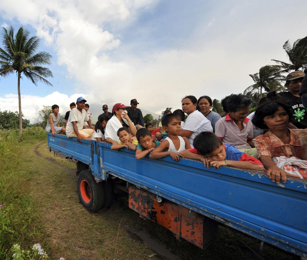 8. Жители деревни близ вулкана Майон едут на грузовике после того, как власти попросили их покинуть свои дома в городе Гуинобатан в провинции Албай 21 декабря. (AFP/Getty Images/Ted Aljibe)