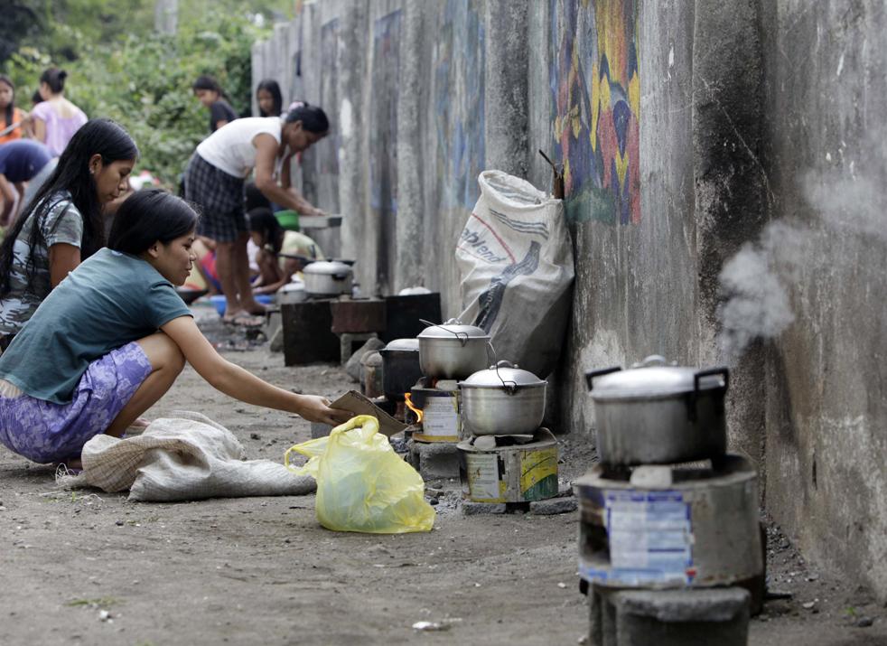 11. Эвакуированные, которых заставили покинуть свои дома, находившиеся вблизи активного вулкана Майон, готовят еду во временном убежище в общественной школе в городе Бакакай, провинция Албай, 20 декабря. (AP/Bullit Marquez)