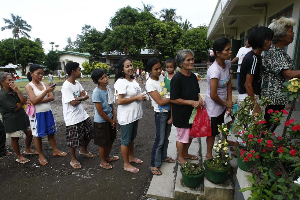 17. Жители, которых насильно эвакуировали из регионов, расположенных недалеко от  вулкана Майон, стоят в очереди за питанием во временном убежище, размещенном в общественной школе города Бакакай в 500 км к юго-востоку от Манилы 19 декабря. (AP/Bullit Marquez)