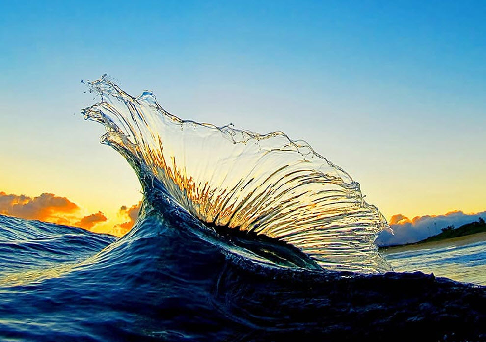 9. «Утренняя фотография волны на восходе солнца, которая столкнулась со следующей за ней волной, отчего в воздухе получилась невообразимо красивая арка, похожая на рыбу парусник». (Clark Little)