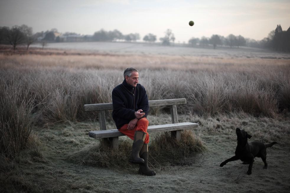 2. Мужчина бросает мячик своей собаке, сидя на замерзшей скамейке в Ричмонд-парке 16 декабря в Лондоне. Холодный циклон должен принести снег в некоторые части Великобритании, а температура – упасть до -4 градусов по Цельсию. К концу недели в столице Англии ожидают сильный снегопад. (Getty Images/Dan Kitwood)