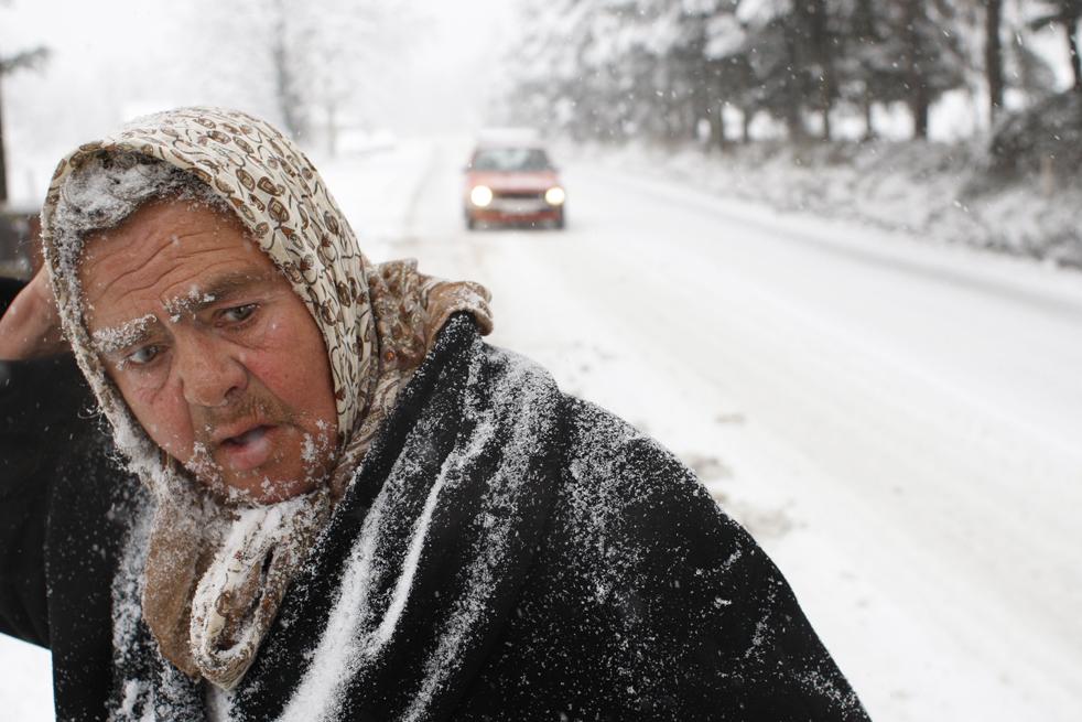 4. Боснийская женщина идет по главной дороге в ожидании общественного транспорта во время пробок, вызванных снегопадом недалеко от Сараево, Босния, 15 декабря. Снег, выпавший ночью, посеял на дорогах страны хаос и вызвал в некоторых отдаленных районах сбой в подаче электричества. (AP/Amel Emric)
