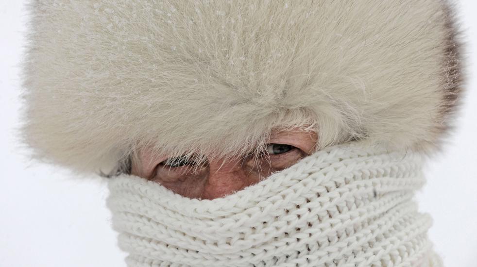 5. Эрна Вэхтер пытается согреться в своей белой меховой шапке и шарфе после снегопада в Тюрингенском лесу недалеко от Оберхофа, Германия, 15 декабря. По прогнозам температура не поднимется здесь еще несколько дней. (AP/Jens Meyer)