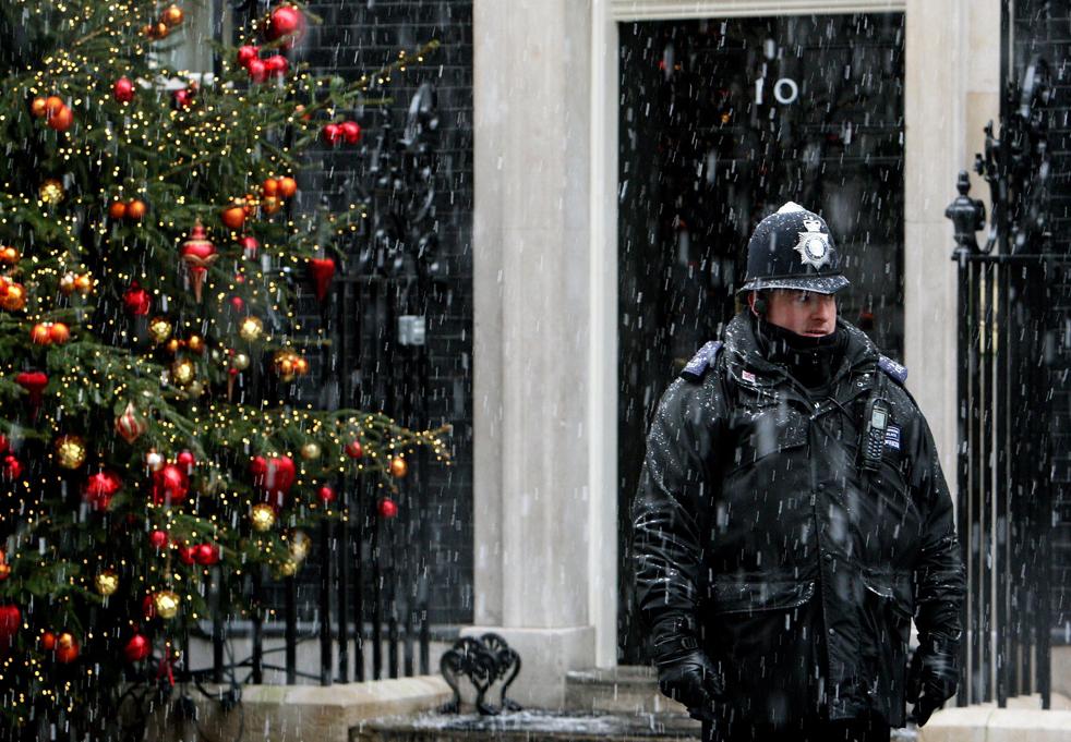 9. Офицер полиции стоит у дома № 10 британского премьер-министра Гордона Брауна по улице Downing Street во время снегопада в центре Лондона 16 декабря. В некоторых сельских районах страны температуры упали до -6° по Цельсию, а метеорологические службы предупредили, что в среду в юго-восточной части Англии может выпасть до 1-2 см снега. (AP/Dominic Lipinski)