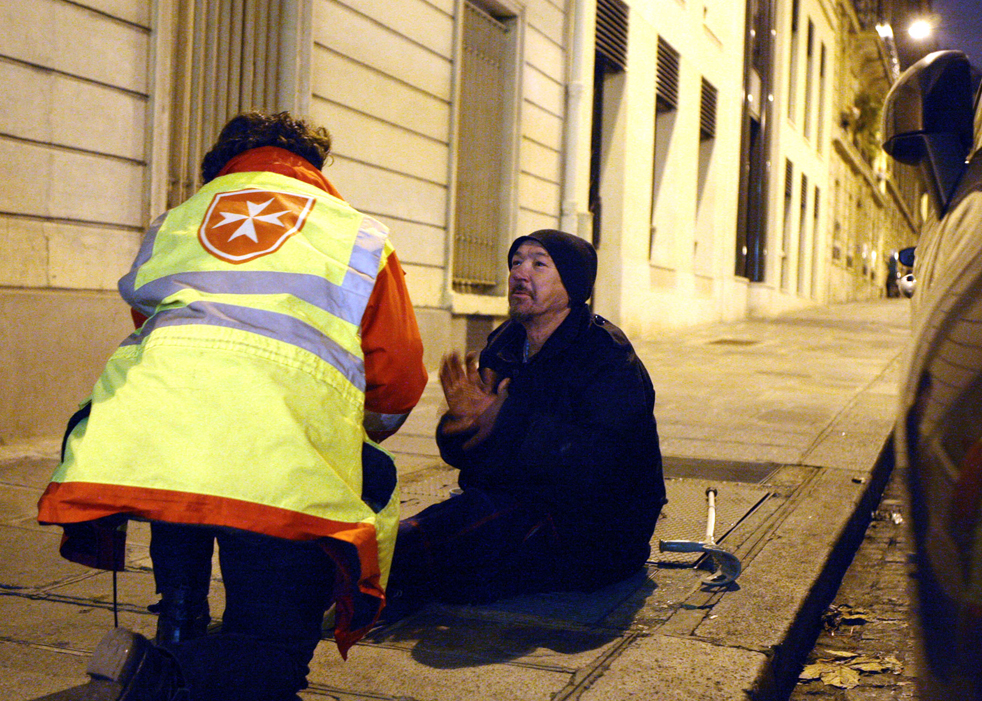 10 .Добровольцы из общества «Malta Order Society» заботятся о бездомном человеке вечером 15 декабря в Париже, где шкала термометра упала до -10 градусов по Цельсию. (AP/Remy de la Mauviniere)