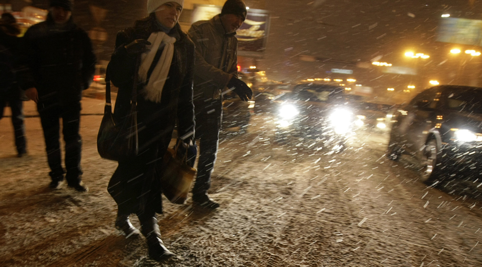 14. Люди переходят улицу во время снегопада в Москве 7 декабря. Сильные снегопады впервые выпали в Москве в этом сезоне, а температура упала до -5 градусов после рекордно теплой погоды в начале Декабря. (AP/Ivan Sekretarev)