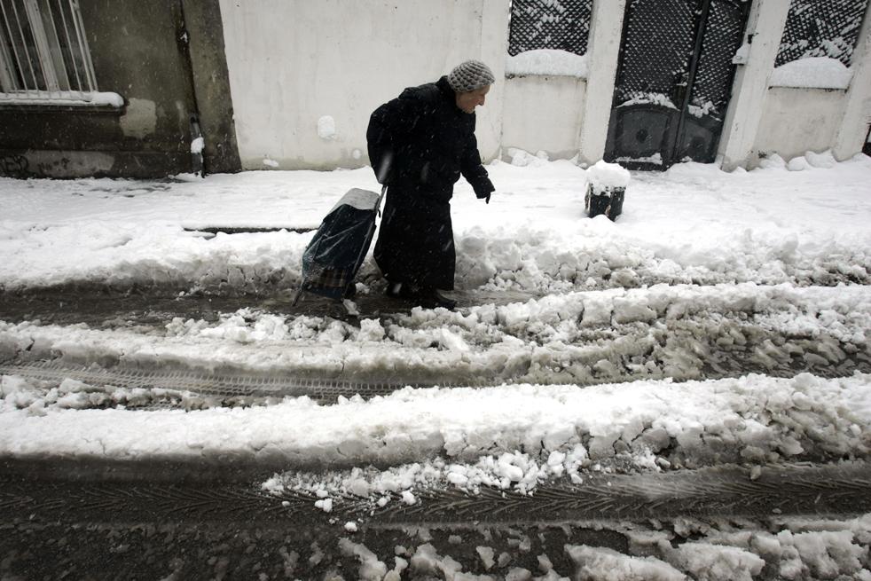 15. Женщина тащит за собой тележку по заснеженной улице в Белграде, Сербия, 15 декабря. Метеорологи предсказывают сильные снегопады в Белграде на этой неделе. (AP/Marko Drobnjakovic)