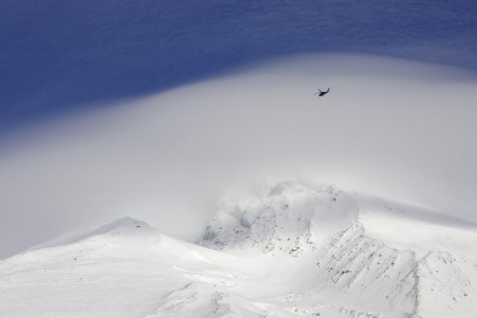 18. Вертолет Национальной гвардии Орегона летит над окутанной облаками горой Худ в поисках двух пропавших альпинистов. Снимок сделан с Тимберлайн Лодж в Говернмент Кэмп, Орегон, 14 декабря. (AP/Don Ryan)