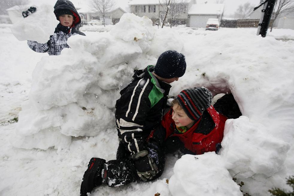 20. 9-летний Эндрю Роули (в центре) и 11-летний Грант Писке (справа) играют в снежной крепости, пока их друг 12-летний Кайл Альт (слева) продолжает строить ее в Маренто, штат Иллинойс, 9 декабря. В среду многие школы были закрыты из-за снегопадов. (Chicago Tribune/Lane Christiansen)