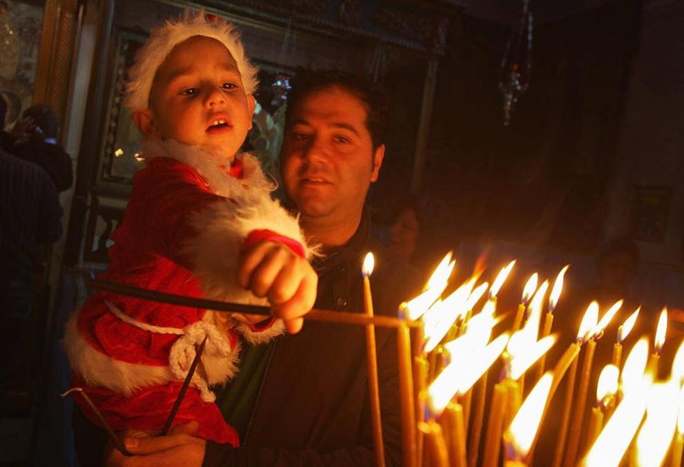 5. Маленький палестинский христианин в костюме Санты зажигает свечу со своим отцом 20 декабря. (David Silverman, Getty Images)