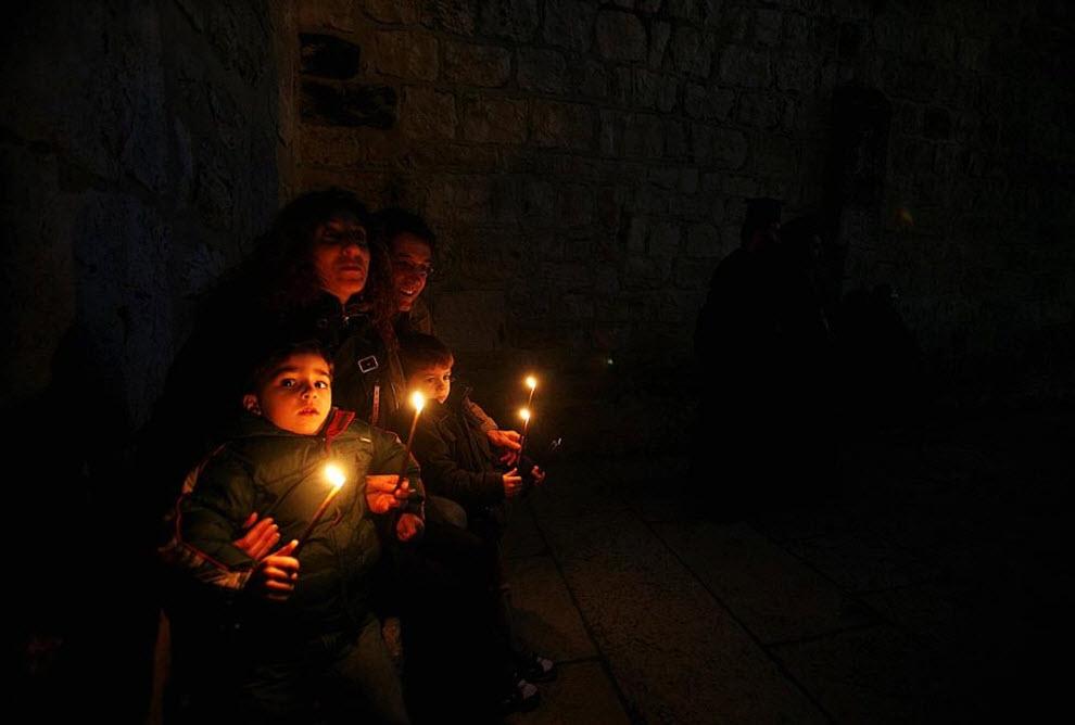 7. Члены палестинской христианской семьи держат свечи перед Гротом Рождества Христова и смотрят, как мэр библейского города зажигает елку на площади Мангер 15 декабря. (Musa Al-Shaer, AFP / Getty Images)