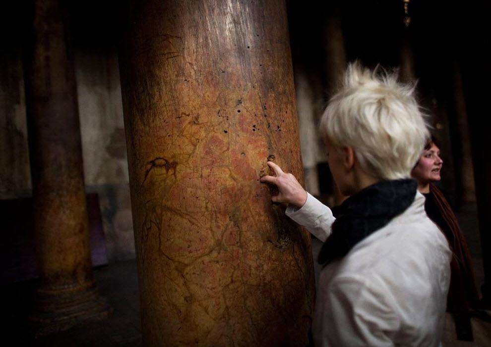8. Посетительница кладет пальцы на дырочки в форме распятия на одной из древних колонн в церкви 21 декабря. (Uriel Sinai, Getty Images)