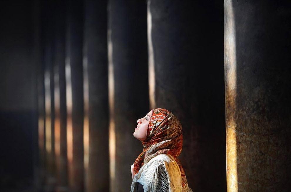 16. Ноур – палестинка, исповедующая ислам, стоит в свете, просачивающемся в верхнее окно и отбрасывающем лучи на древние мраморные колонны, во время посещения Грота Рождества Христова 20 декабря. (David Silverman, Getty Images)