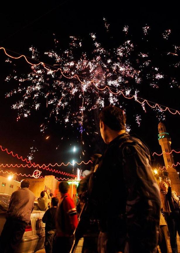 17. Палестинский офицер службы безопасности повернулся, чтобы посмотреть салют на площади Мангер у Грота Рождества Христова 15 декабря. (Nasser Shiyoukhi, AP)