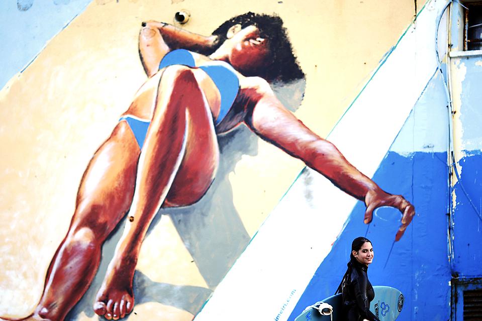 3. Девушка-серфер проходит мимо граффити на стене, поймав несколько волн в Средиземном море в Телль-Авиве. Серферам посчастливилось прокатиться на волнах, высота которых доходила до двух метров. (Ariel Schalit/Associated Press)