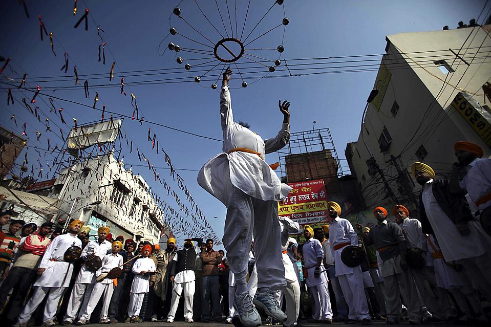 6. Сикх выступает на религиозной процессии накануне годовщины рождения 10-го сикха Гуру – Гобинда Сингха – у Золотого храма в Амритсаре, Индия. (Altaf Qadri/Associated Press)