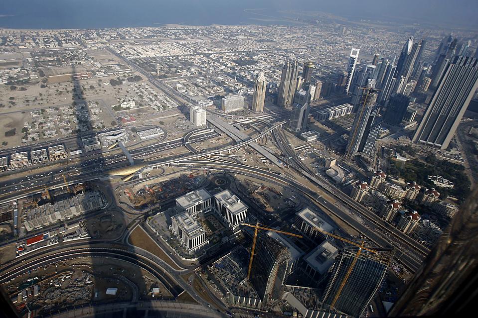 7. Сверкающая стеклянно-металлическая башня Бурдж Калифа, которую открыли в понедельник, отбрасывает длинную тень в Дубае. Высота небоскребе, переименованого в честь лидера соседнего Абу-Даби, составляет 828 метров. (Kamran Jebreili/Associated Press)