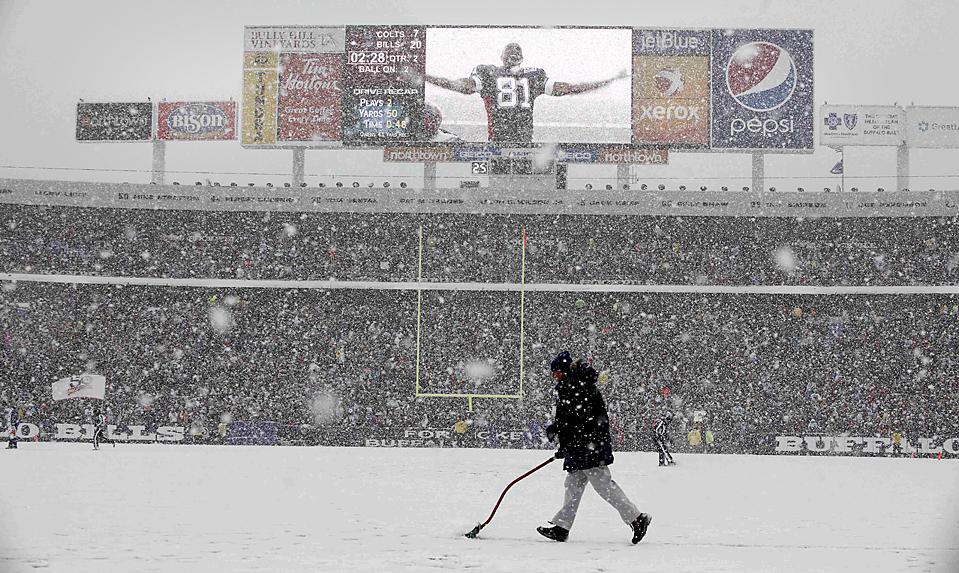15. На экране показывают Террелла Оуэнса из «Buffalo Bills», радующегося тачдауну, пока рабочий убирает снег с поля на игре против «Indianapolis Colts» в Орчард Парке, Нью-Йорк. «Buffalo Bills» выиграли со счетом 30-7. И все же тренер команды Пери Фьеюлл и его команда были уволены. (David Duprey/Associated Press)