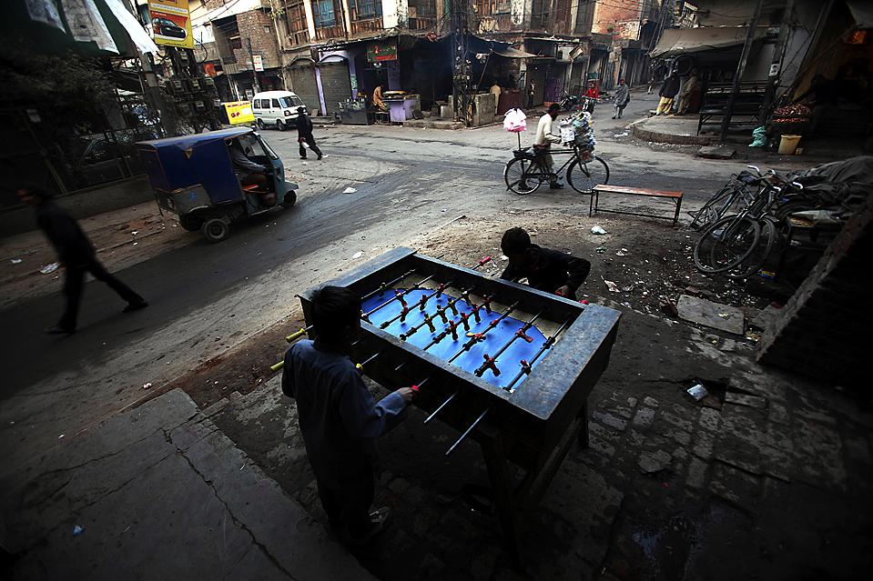 16. Мальчики играют в настольный футбол на улице Лахора, Пакистан. (Muhammed Muheisen/Associated Press)