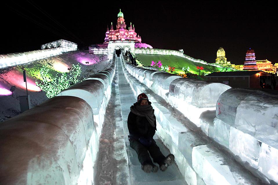 2. Женщина едет с ледяной горки на Международном фестиваля льда в Харбине, провинция Хэйлунцзян, Китай. (Ng Han Guan/Associated Press)