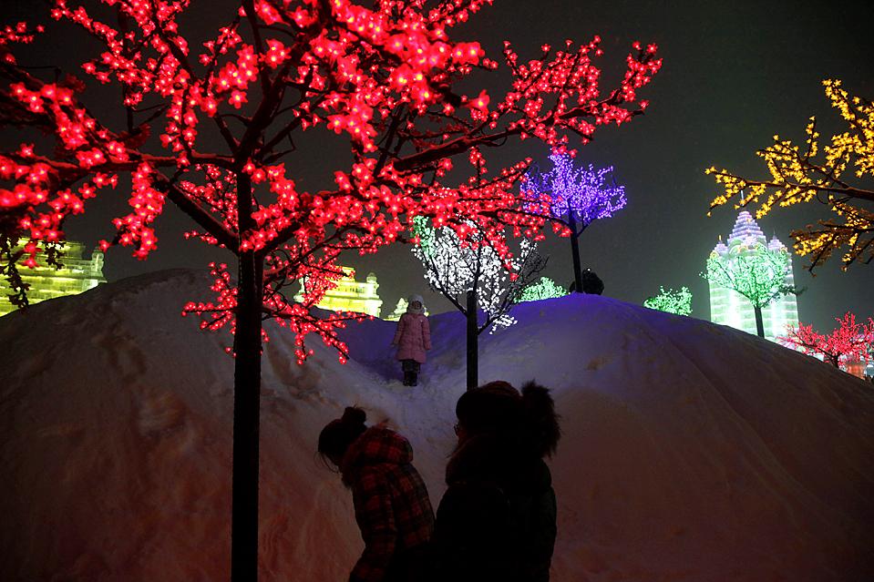 1. Девочка стоит среди деревьев с разноцветными гирляндами на Международном фестивале снега и льда в Харбине, провинция Хэйлунцзян, Китай. На 26-ом по счету ежегодном фестивале есть ледяные скульптуры пагод, сфинкса и многих других. (Ng Han Guan/Associated Press)