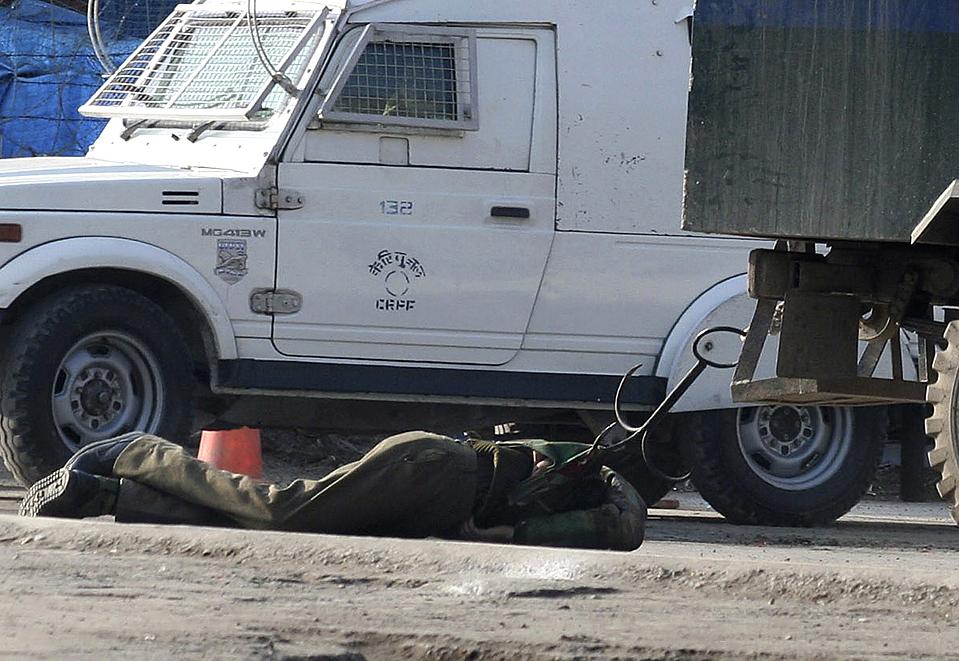10. Полицейские в автомобиле пытаются оттащить тело убитого товарища с места перестрелки с боевиками в Шринагаре, Индия. Боевики бросали гранаты и открыли огонь, в результате чего погиб полицейский. (European Pressphoto Agency)