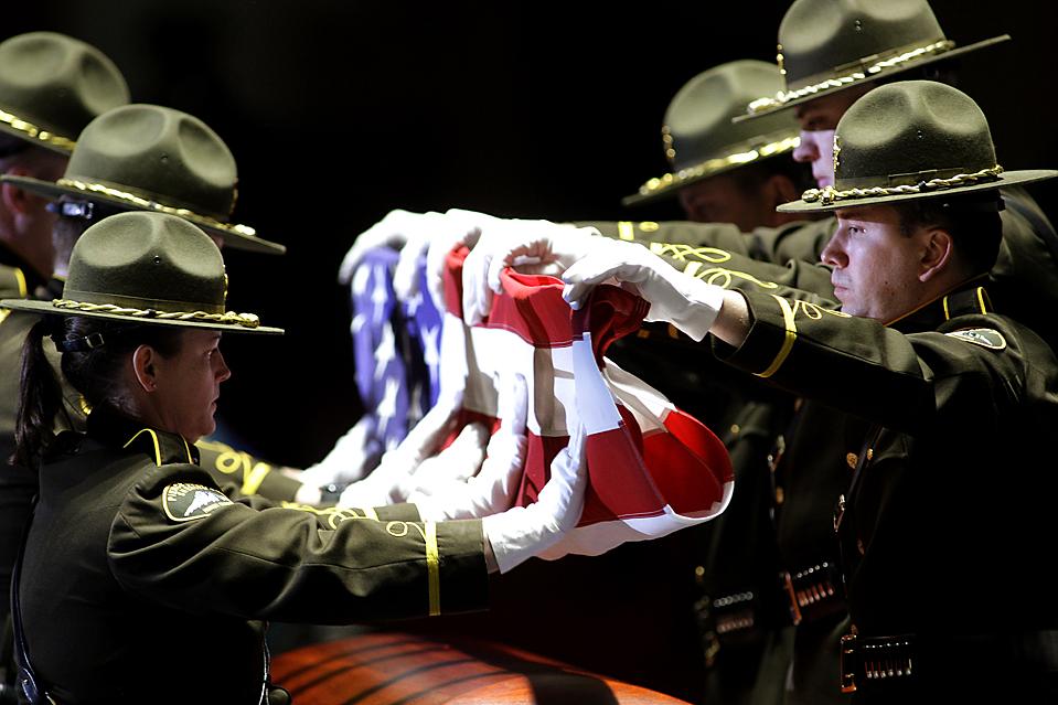 11. Заместители шерифа округа Пирс, Вашингтон, складывают флаг, лежавший на гробу убитого заместителя шерифа Кента Манделла во время похорон в Такоме, штат Вашингтон. Мистер Манделл был застрелен в прошлом месяце во время разрешения бытового скандала. (Ted S. Warren/Associated Press)