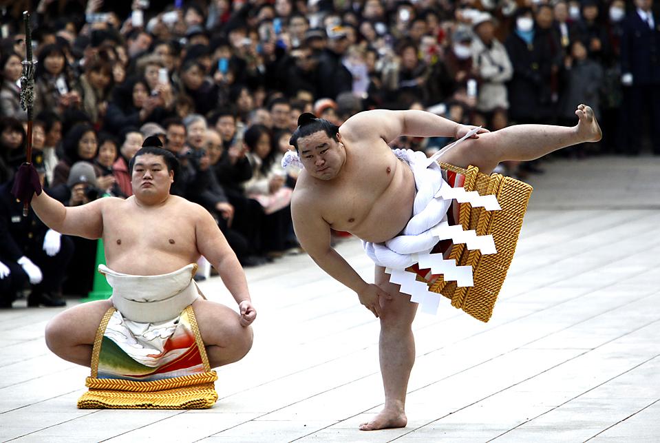 12. Йокозуна Асашору (справа) и его помощник исполняют церемониальные притопы у храма Меидзи в Токио. (Shizuo Kambayashi/Associated Press)