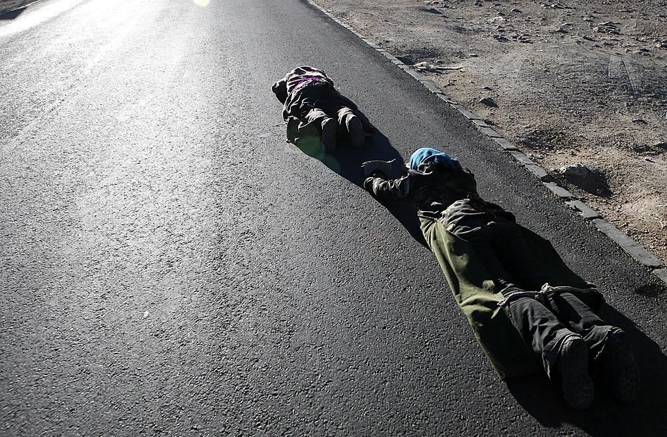 15. Тибетцы исполняют ритуал Ке Чанг Ту, ложась на землю лицом вниз через каждые три шага во время своего паломничества в Лхасу. Паломничество может длиться месяцы, а то и годы. (Xin Ning/European Pressphoto Agency)