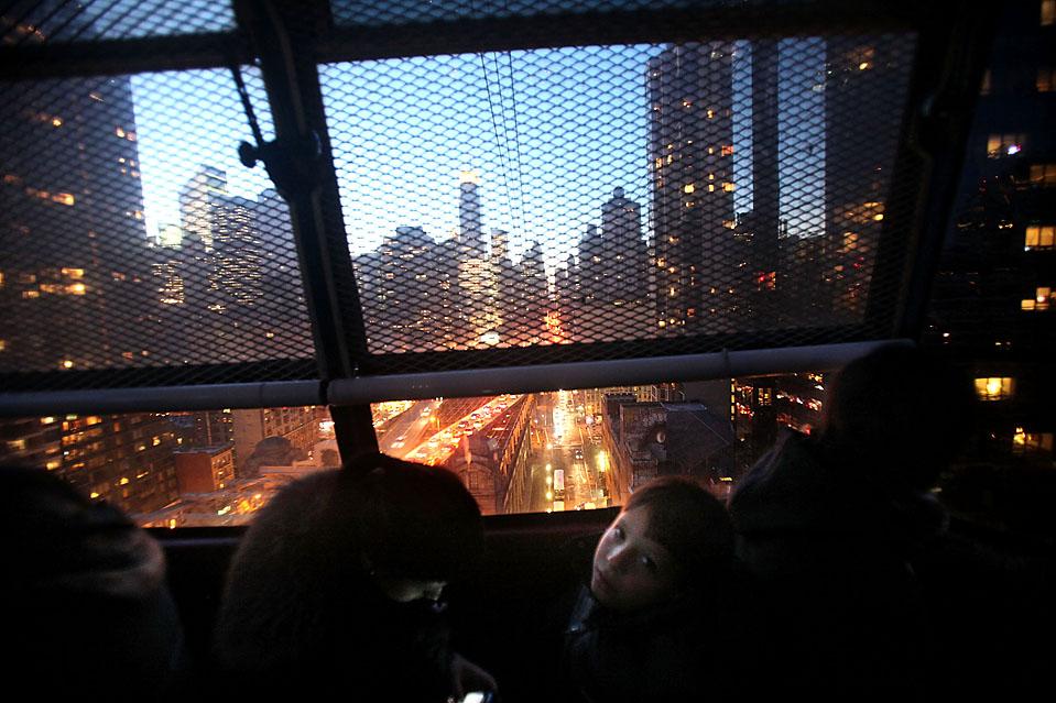 16. Люди едут в трамвае Рузвельт-Айленд, проезжающим над Манхэттеном в Нью-Йорке. Впервые с 1990 года Нью-Йорк восстановил свое звание любимого туристического города Америки. В прошлом году город посетило 45,3 миллиона туристов. (Mario Tama/Getty Images)