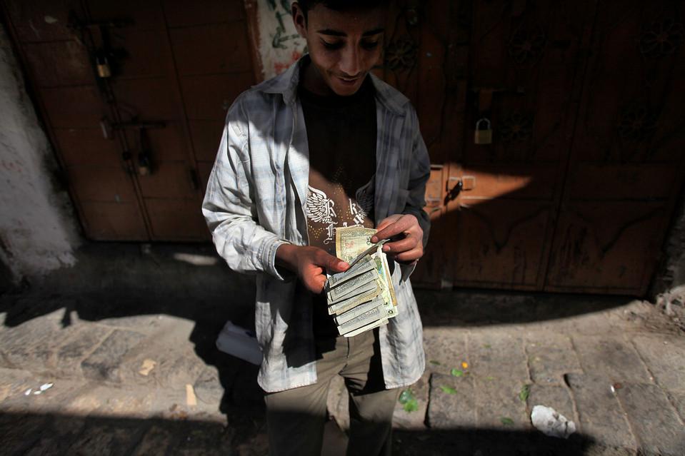 6. Кат – наркотическое растение, которое жуют многие йеменцы весь день. На фото: молодой человек считает деньги, продав все свои запасы ката. (Karim Ben Khelifa for The Wall Street Journal)