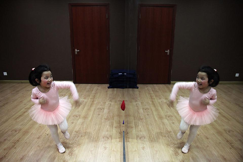 3) Ученица балетной школы в Шанхае из младшего класса (для девочек 3-5 лет), улыбается своему отражению во время урока. (REUTERS/Nir Elias)
