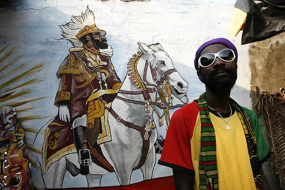8 ) Участник движения Растафари стоит около рисунка, изображающего покойного эфиопского императора Хэйла Селэсси. Снимок сделан во время митинга в поддержку действующего президента Лорента Гбэгбо, которые проводятся перед долго откладываемыми президентскими выборами в Кот-д'Ивуар. (Luc Gnago/Reuters)