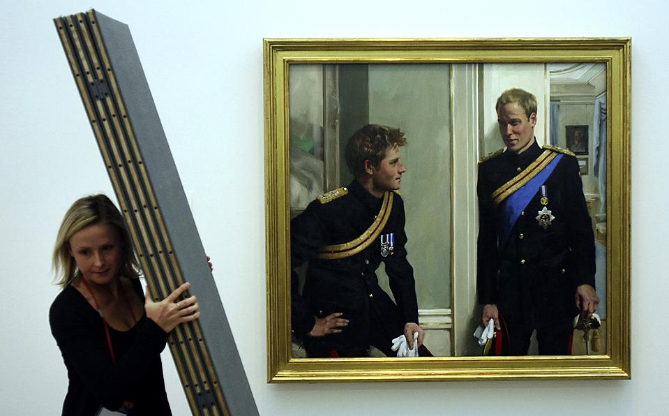 9) Девушка снимает чехол с нового двойного портрета принцев Уильяма и Гарри (художник Никки Филиппс), который представили в Национальной Портретной галерее в Лондоне в среду. (Alastair Grant/Associated Press)