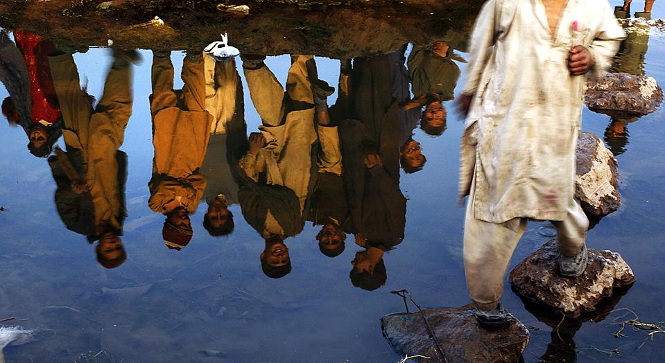 11) Отражение афганских беженцев в маленькой речушке в пакистанском городе Равалпинди. (Muhammed Muheisen/Associated Press)