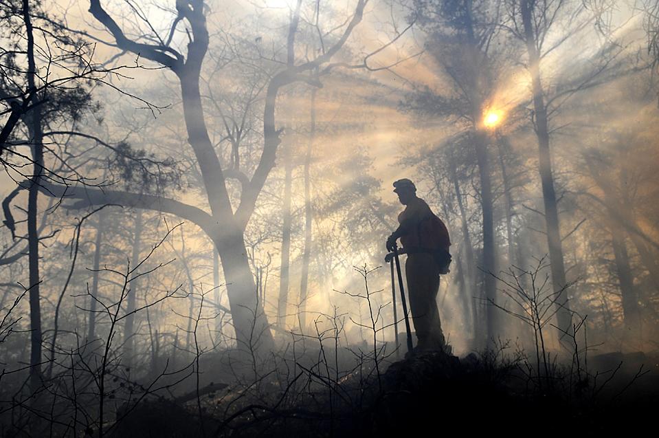 12) Член пожарной команды наблюдает за своим участком во время управляемого пожара в государственном парке Кроудерс Маунтэйн в Северной Каролине. Пожарные сжигают слой хвороста для того, чтобы предотвратить возможные внезапные возгорания. (John D. Simmons/The Charlotte Observer via Associated Press)