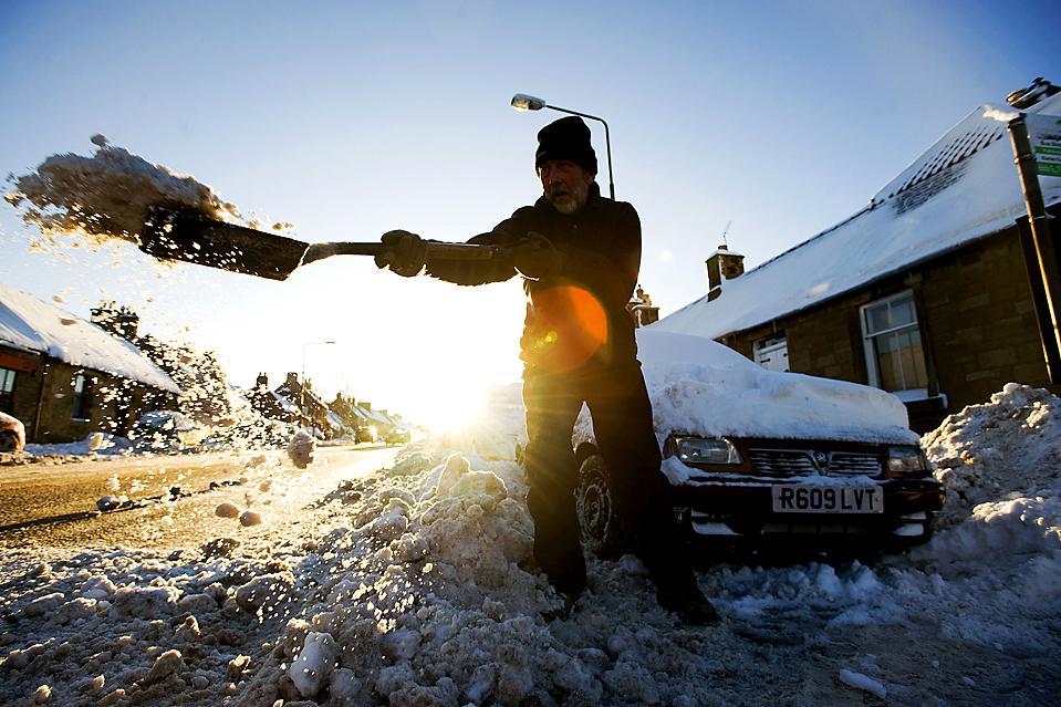 13) Мужчина откапывает свой автомобиль в шотландском городе Пасхэд, во время сильных морозов, которые продолжаются в Великобритании. (Derek Blair/Agence France-Presse/Getty Images)
