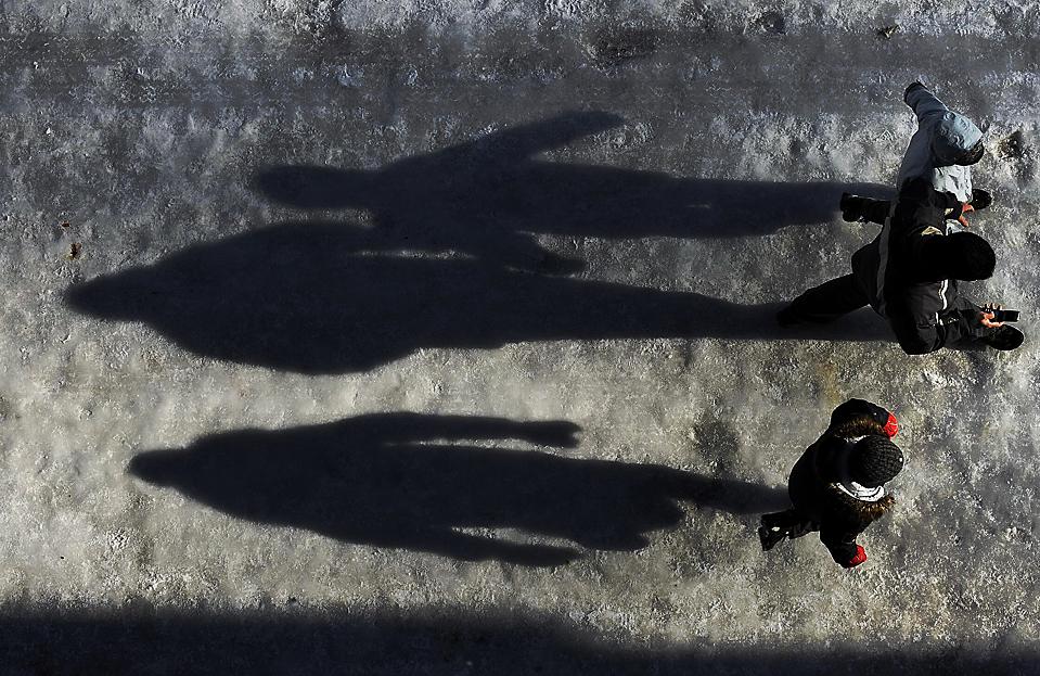 9. Люди идут по заледенелой улице, отбрасывая тень, в Витории, Испания. В стране господствуют морозы. (Alvaro Barrientos/Associated Press)