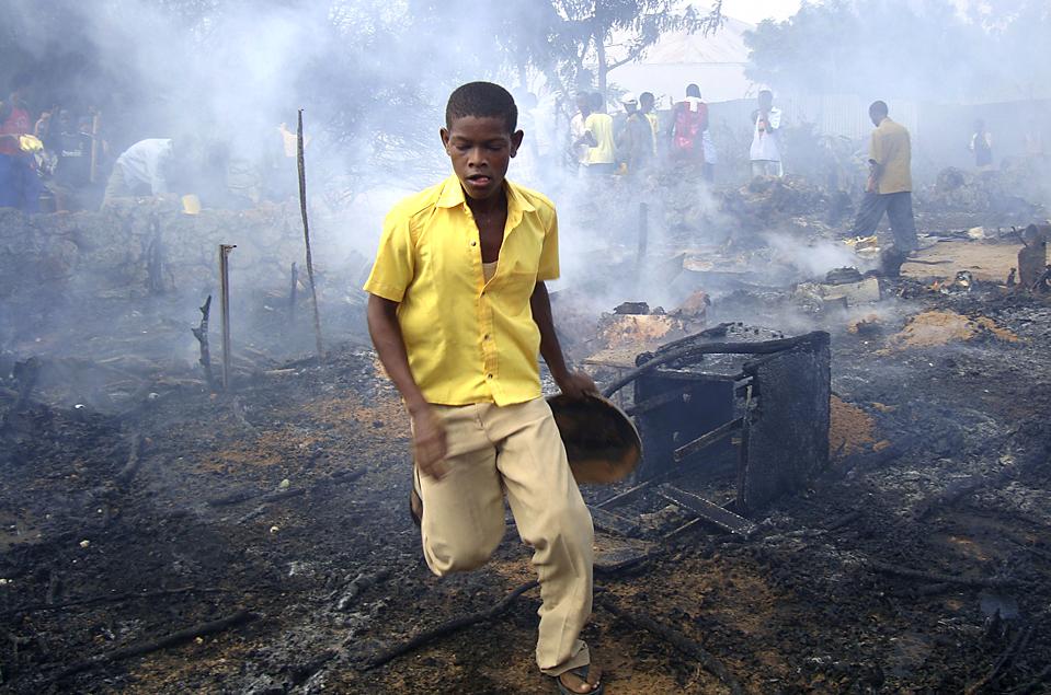 8. Мальчик пытается потушить пожар, поглотивший лагерь внутренне перемещенных лиц в районе Могадишу Булохубей. (Feisal Omar/Reuters)