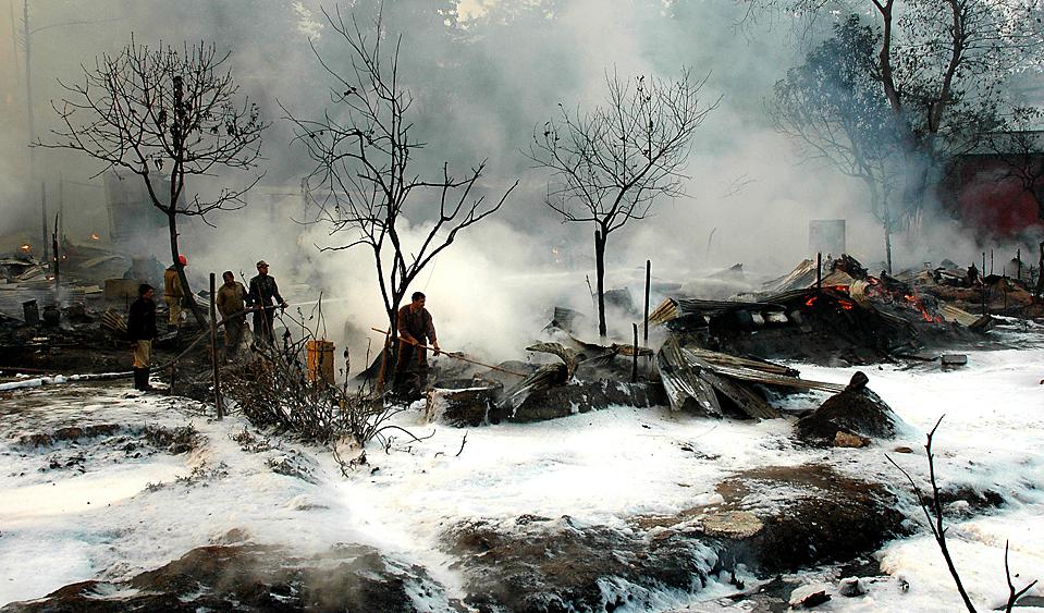 9. Пожарные тушат огонь на нефтеперерабатывающем заводе в Гувахати, Индия. Власти сообщают, что огонь, возникший из-за утечки трубы на заводе, поглотил 100 домов всего за два часа. (Biju Boro/Agence France-Presse/Getty Images)