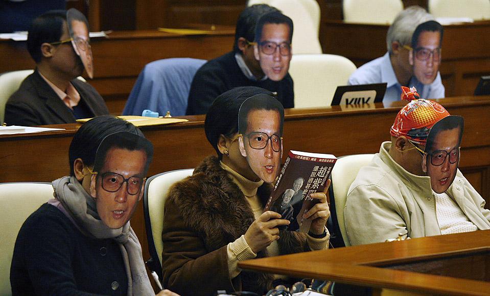 4. Демократические законодатели в масках заключенного в тюрьму китайского диссидента Лю Сяобо во время законодательного собрания по случаю его дела в Гонконге. Лю отбывает 11 лет заключения за проведение кампаний за политическую свободу. (Bobby Yip/Reuters)