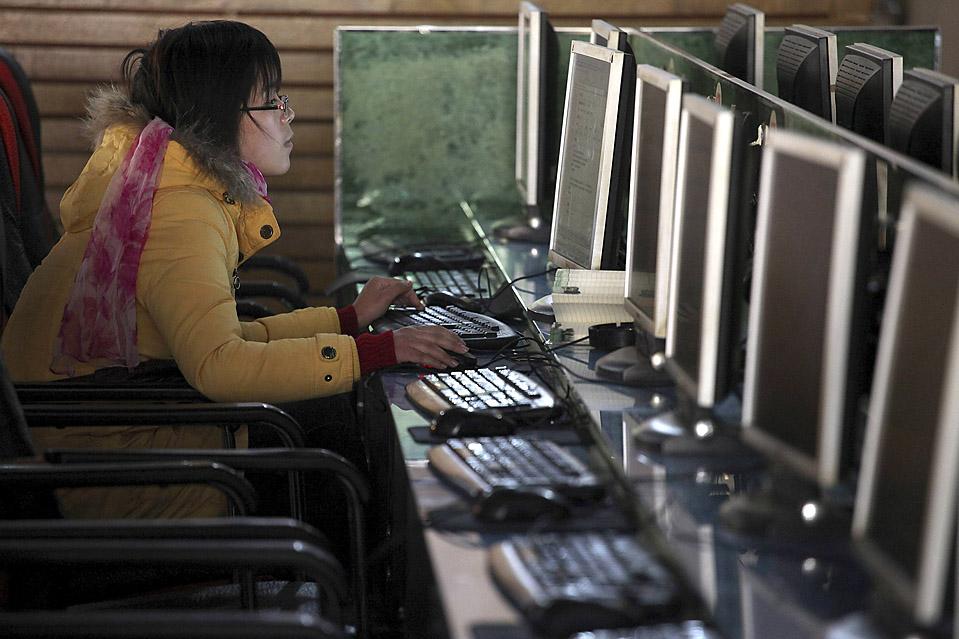6. Женщина сидит за компьютером в интернте-кафе в Шанхае. Компания «Google» сообщила во вторник, что прекращает цензурирование китайского сайта Google.cn и может вообще прекратить работу в этой стране  из-за недавних кибер-атак. (Nir Elias/Reuters)