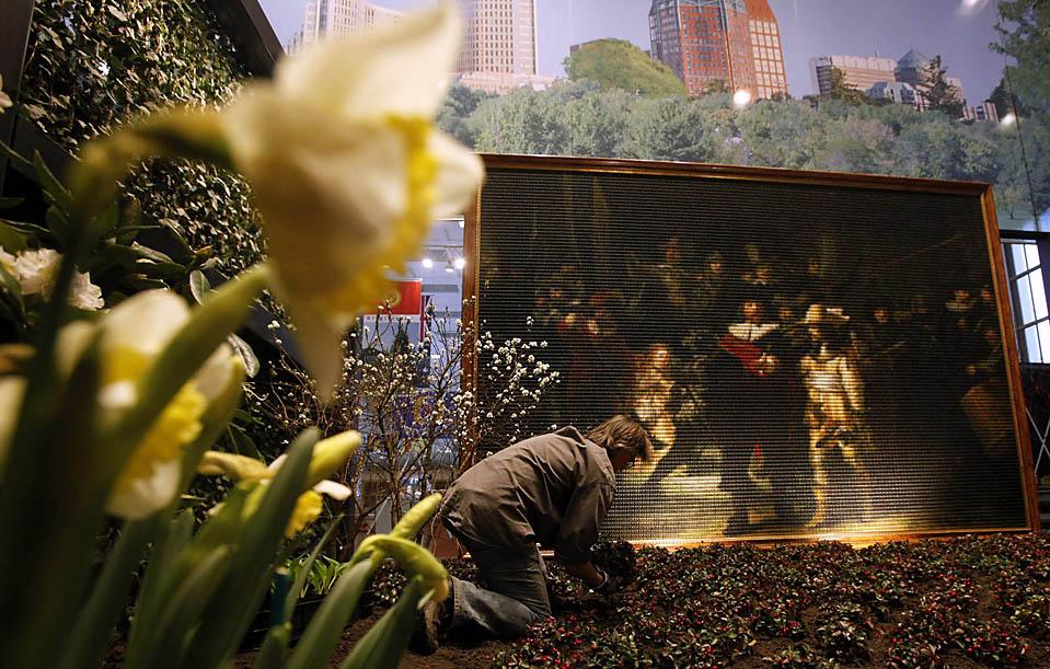 8. Садовник работает рядом с копией картины Рембрандта «Ночной дозор», сделанной из 30 000 маленьких деревяшек на Международной «зеленой» ярмарке в Берлине. (Tobias Schwarz/Reuters)