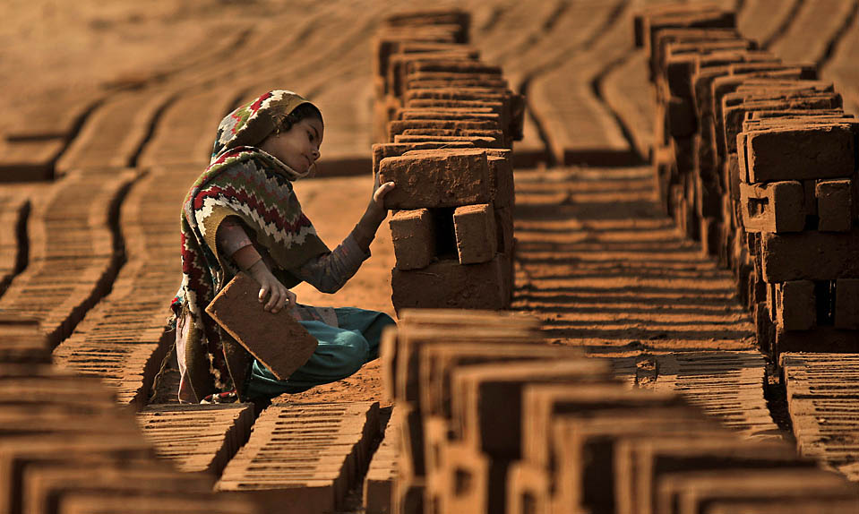 13. Девочка расставляет кирпичи на заводе недалеко от Исламабада, Пакистан. (Muhammed Muheisen/Associated Press)